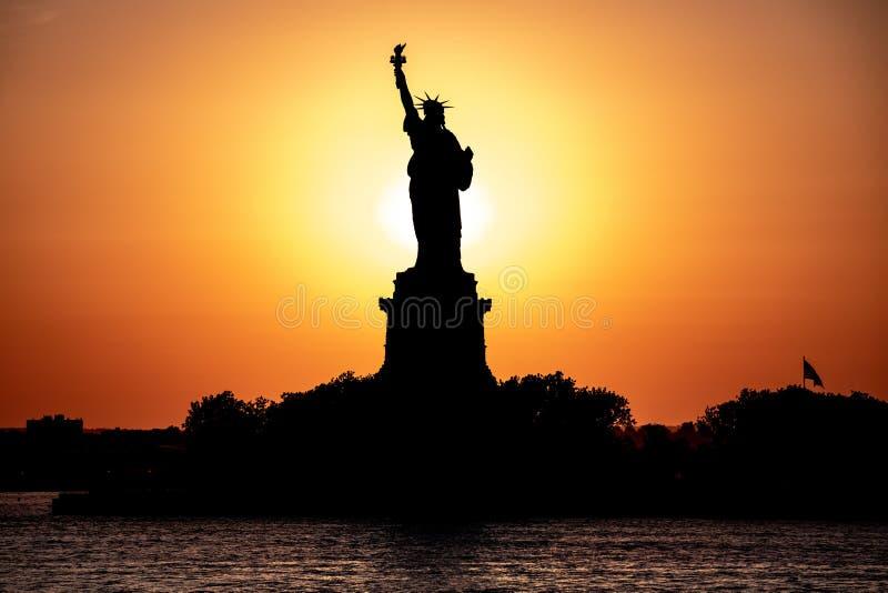 Vista escénica de la estatua de la libertad en una puesta del sol fotos de archivo libres de regalías