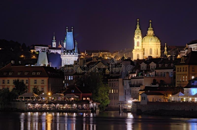 Vista escénica de la noche Praga Río de Moldava con muchos cafés y restaurantes en los edificios en la orilla del río foto de archivo