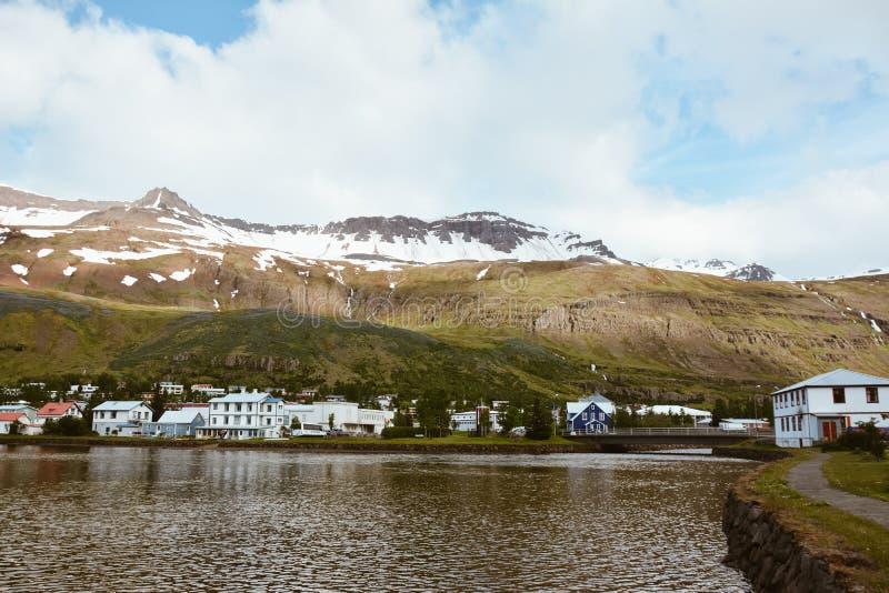 Vista escénica de la pequeña ciudad Seydisfjordur en Islandia del este en verano con el lago y la nieve en las montañas imágenes de archivo libres de regalías