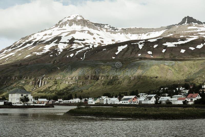 Vista escénica de la pequeña ciudad Seydisfjordur en Islandia del este en verano con el lago y la nieve en las montañas imagen de archivo