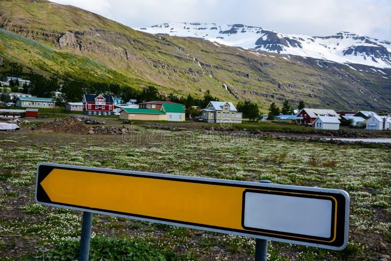 Vista escénica de la pequeña ciudad Seydisfjordur en Islandia del este en verano con nieve en las montañas foto de archivo libre de regalías
