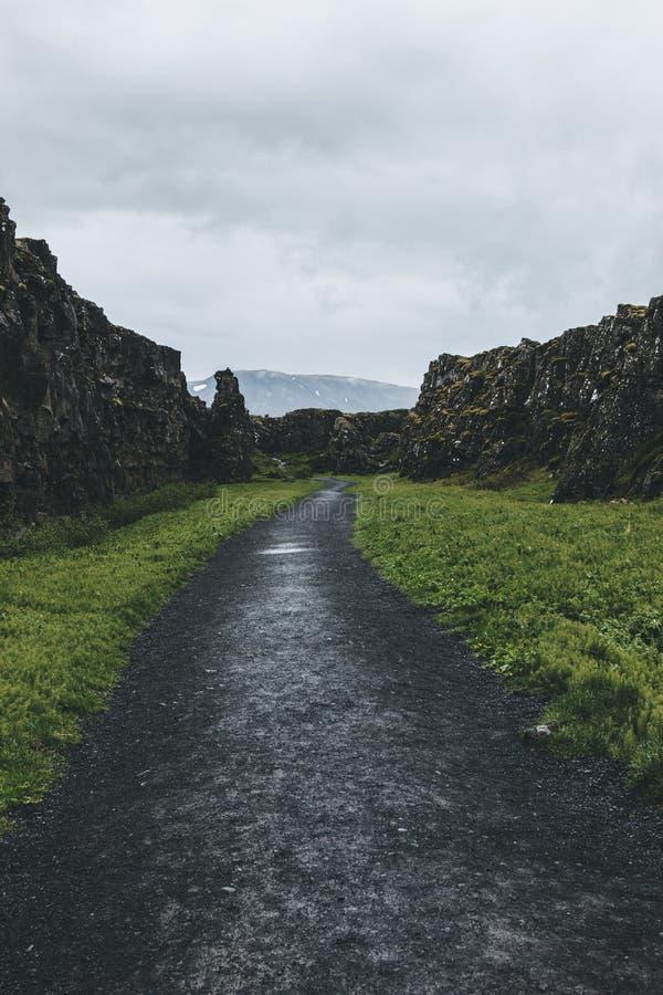 vista escénica de la trayectoria en montañas debajo del cielo nublado en el parque nacional de Thingvellir imagenes de archivo