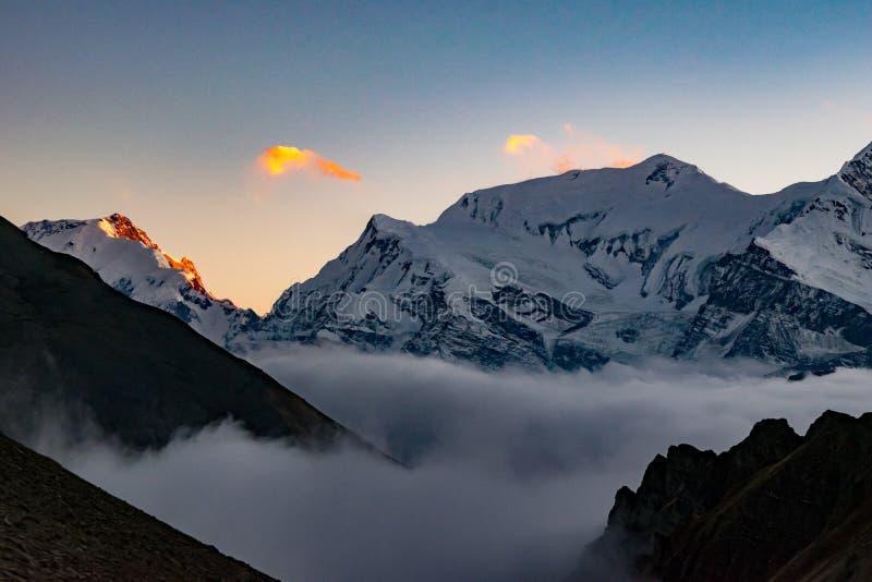 Vista escénica de las montañas y de las nubes después de la puesta del sol, Himalaya de Annapurna fotografía de archivo