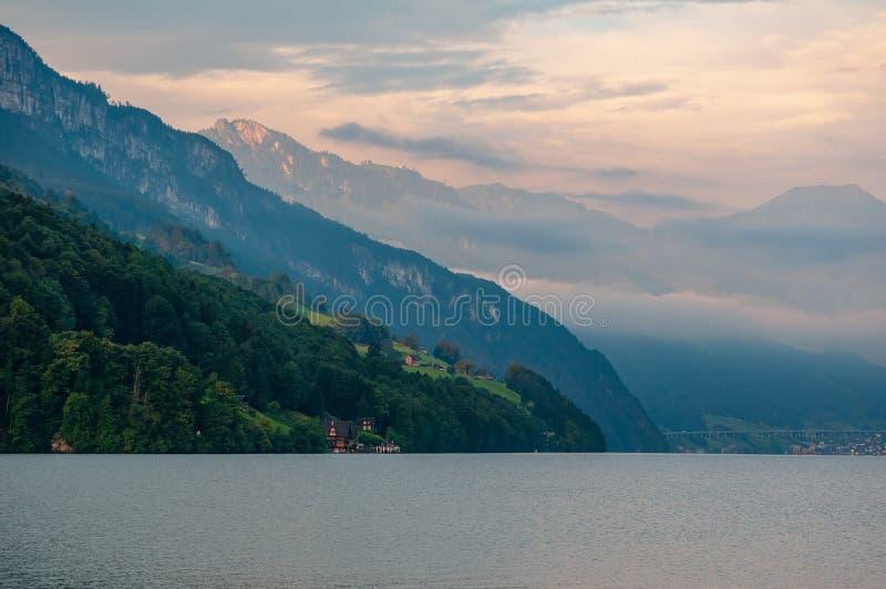 Vista escénica de montañas sobre el lago lucerne debajo del cielo pintoresco, cantón de Uri, Suiza foto de archivo libre de regalías