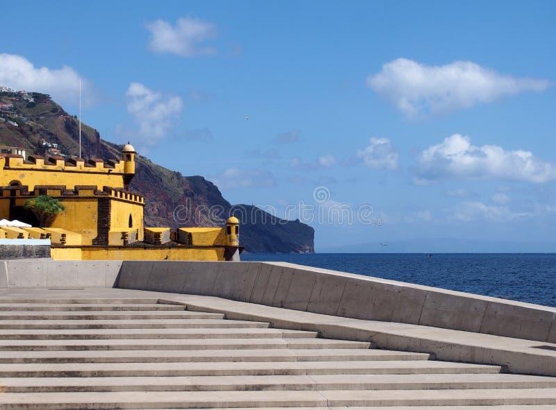 vista escénica de pasos concretos en la orilla del mar en Funchal con vistas a los acantilados del océano y el fuerte amarillo de foto de archivo libre de regalías