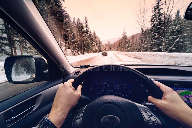 Vista escénica de un camino con paisaje nevado mientras que nieva en la estación del invierno - visión desde el coche imagenes de archivo