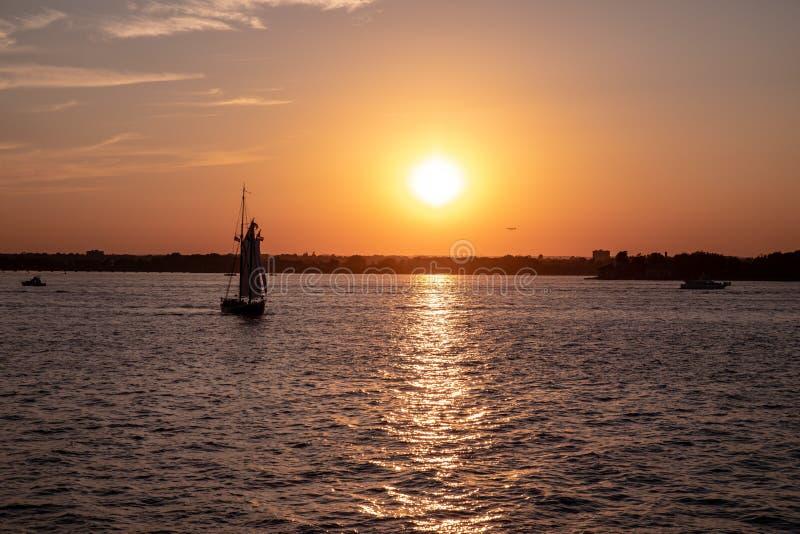 Vista escénica de un pequeño velero en el río Hudson, Nueva York en una puesta del sol fotografía de archivo