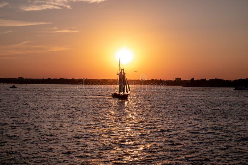 Vista escénica de un pequeño velero en una puesta del sol en un puerto de la ciudad imagen de archivo