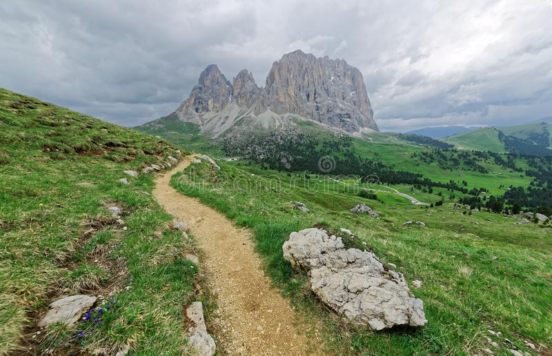 Vista escénica de una pista de senderismo en campos herbosos verdes en las colinas de los picos de montaña rugosos de Langkofel-P imagen de archivo libre de regalías