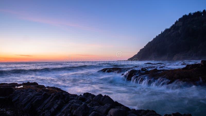 Vista escénica de una puesta del sol sobre el océano Machacando ondas entre en un abismo en el cabo perpetuo, costa de Oregon foto de archivo libre de regalías