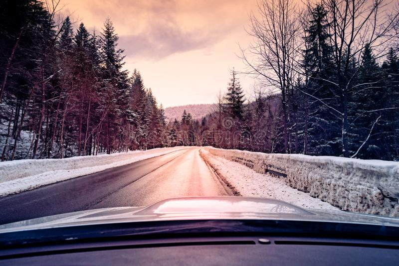 vista escénica del camino vacío con paisaje nevado mientras que nieva en la estación del invierno fotos de archivo libres de regalías