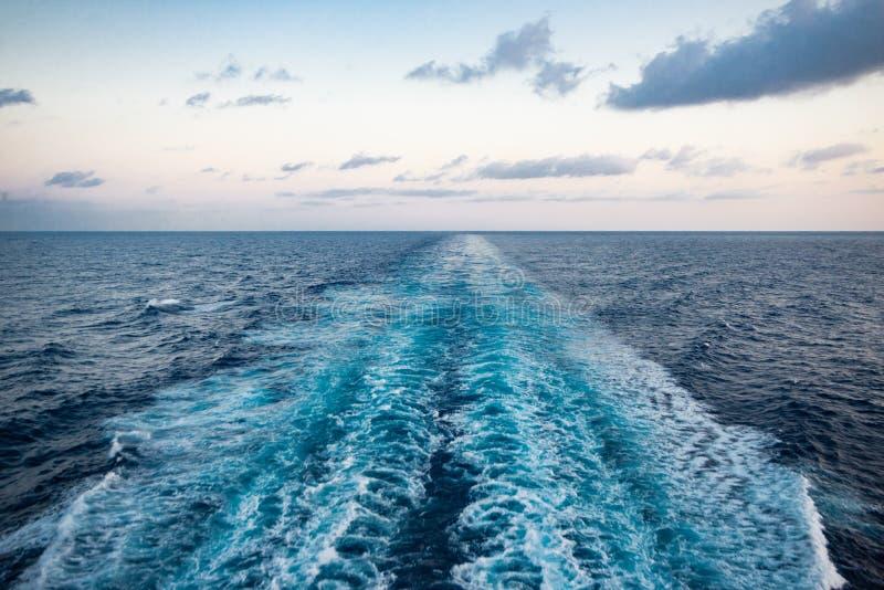 Vista escénica del mar de la popa de un barco de cruceros lujoso, contra la salida del sol en un cielo azul hermoso imágenes de archivo libres de regalías