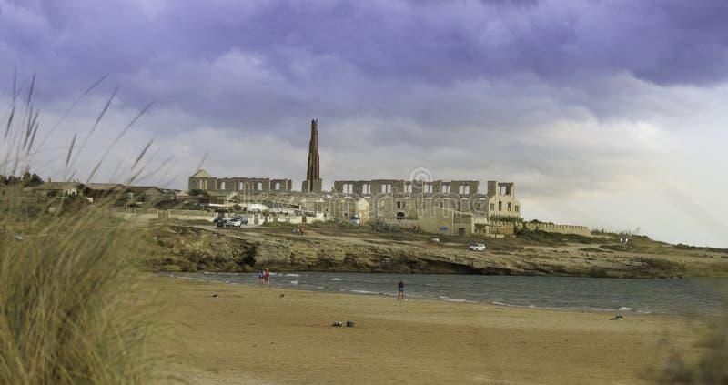 Vista escénica famosa de la fábrica abandonada del molino en la película de Montalbano en la playa de Sampieri en Sicilia foto de archivo