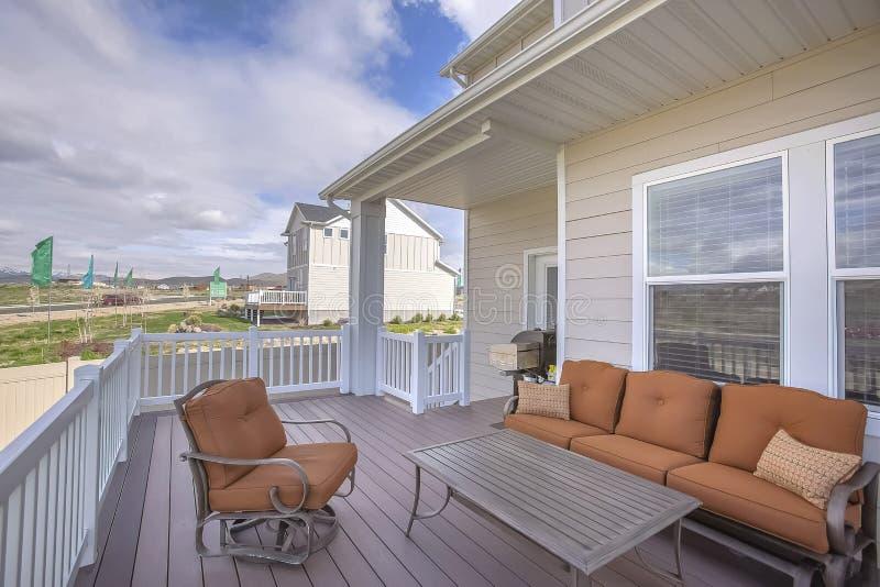 Vista esteriore di una casa con area di disposizione dei posti a sedere sulla piattaforma di legno immagini stock libere da diritti