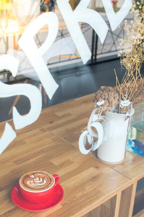 Vista esterna del caffè con arte del latte della tazza di caffè sulla tavola di legno fotografie stock libere da diritti