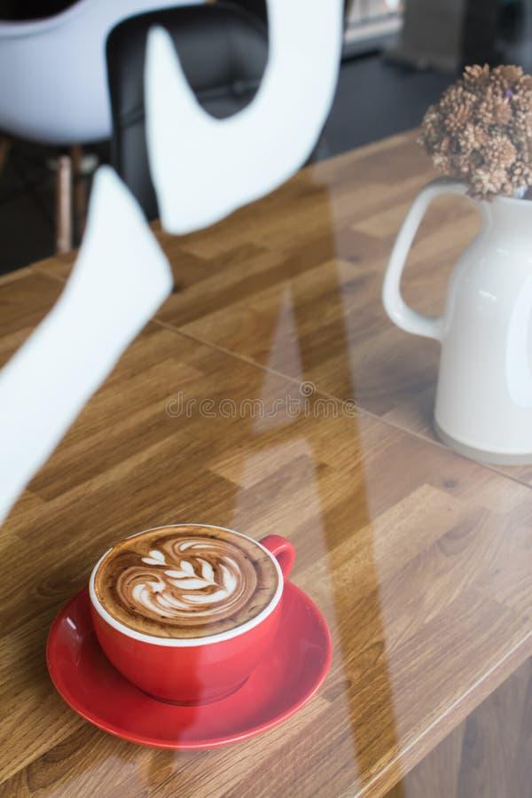 Vista esterna del caffè con arte del latte della tazza di caffè sulla tavola di legno fotografia stock libera da diritti