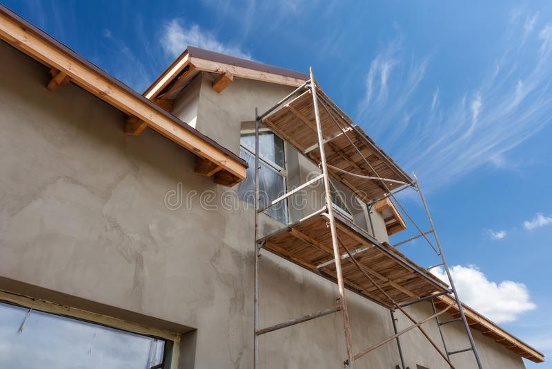 Vista exterior da casa nova sob a construção e a pintura Andaime para o exterior que emplastra em casa fotos de stock royalty free