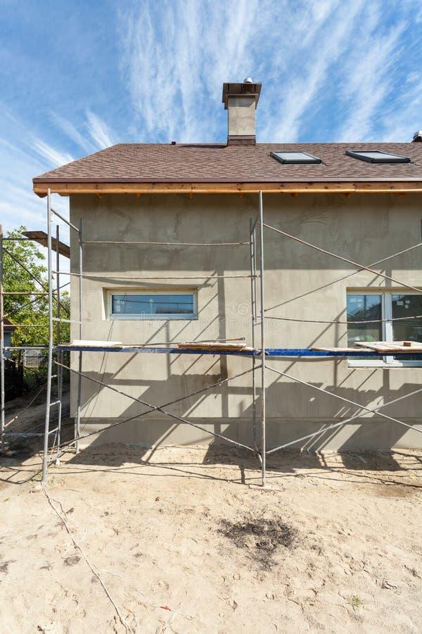 Vista exterior da casa nova sob a construção e a pintura Andaime para o exterior que emplastra em casa a vista lateral imagens de stock royalty free