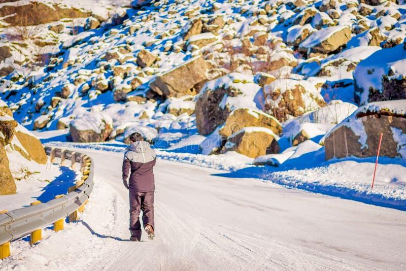 Vista exterior da rua congelada com o homem não identificado que anda na estrada, coberta com a neve durante uma estação do inver imagem de stock
