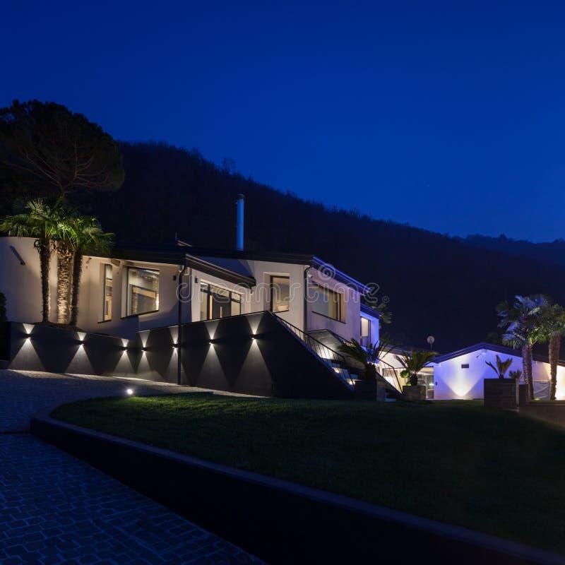 Vista exterior de un chalet de lujo moderno, escena nocturna foto de archivo libre de regalías