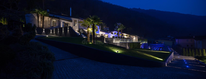 Vista exterior de un chalet de lujo moderno, escena nocturna imagenes de archivo