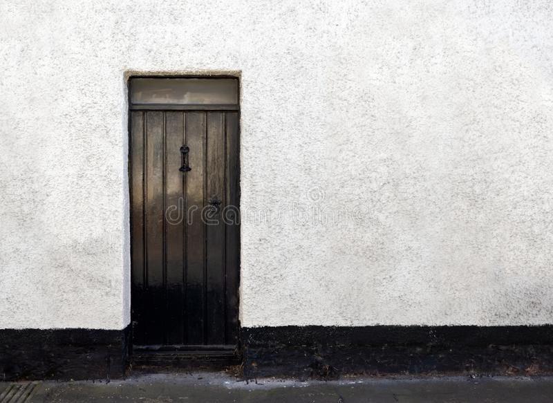 Vista exterior de una cabaña de piedra inglesa vieja hermosa con la puerta imagen de archivo