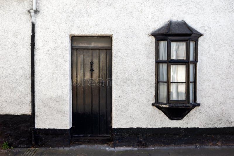 Vista exterior de una cabaña de piedra inglesa vieja hermosa con la puerta y la ventana foto de archivo libre de regalías