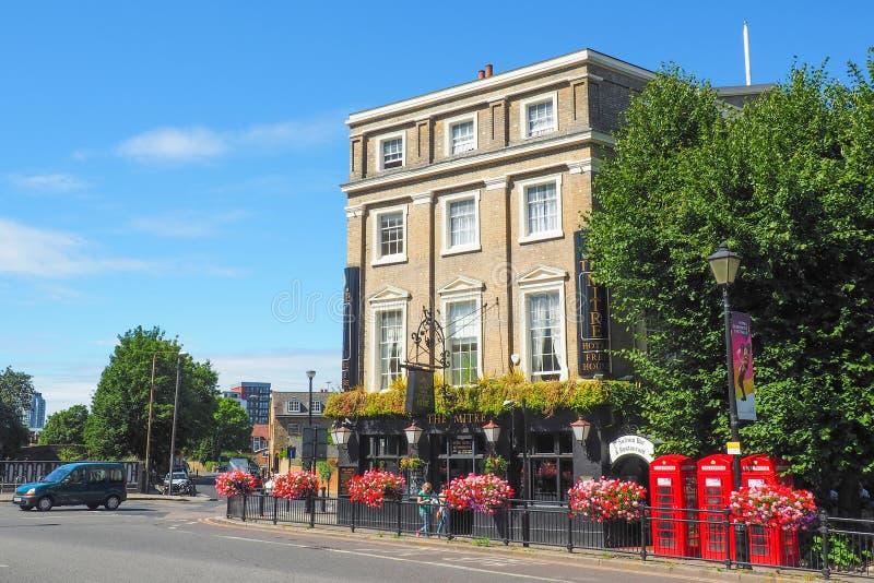 A vista exterior do hotel da mitra em Greenwich, Londres em um dia de verão com as caixas e os povos vermelhos de telefone que pa foto de stock