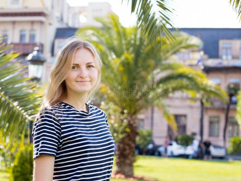 Vista fêmea consideravelmente atrativa dos jovens ao redor, andando na rua da cidade tropical com palmeiras e os carros estaciona fotografia de stock