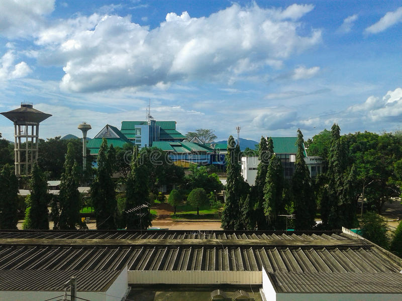 Vista fora da janela Floresta na cidade Coexistência da natureza e da construção Brilhante do céu azul e da nuvem branca fotografia de stock royalty free