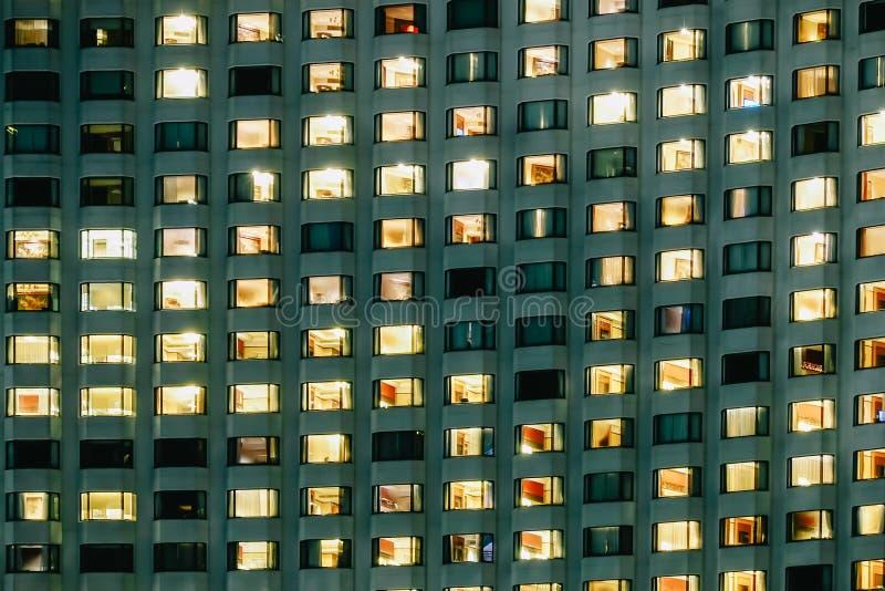 Vista frontal da fachada da noite da construção com muitas janelas e lâmpada nos muitos sala dentro do hotel fotos de stock royalty free