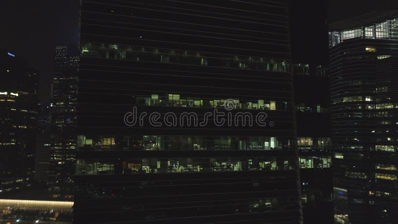 Vista frontal da fachada da noite da construção com muitas janelas iluminadas tiro Fachada a construção do multi-andar de imagem de stock royalty free