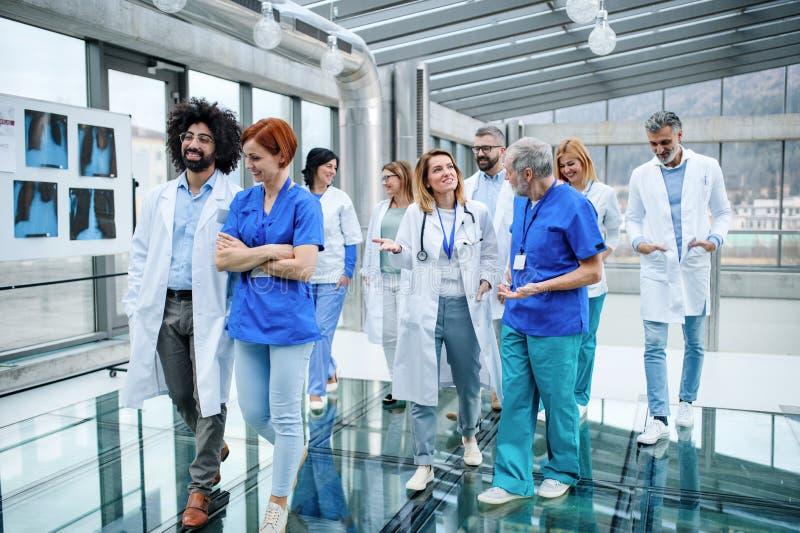 Vista frontal de un grupo de doctores caminando por el pasillo en una conferencia imagenes de archivo