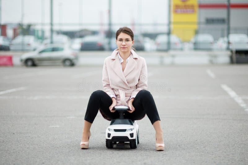Vista frontal de una guapa mujer sentada en un auto infantil en un estacionamiento imagen de archivo