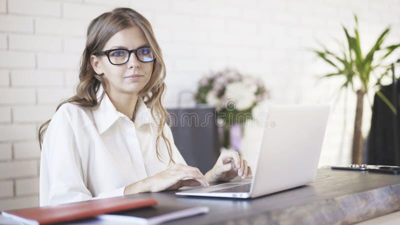 Vista frontale dei vetri d'uso di una giovane bella donna che scrivono al suo computer portatile in ufficio e che esaminano macch fotografia stock libera da diritti