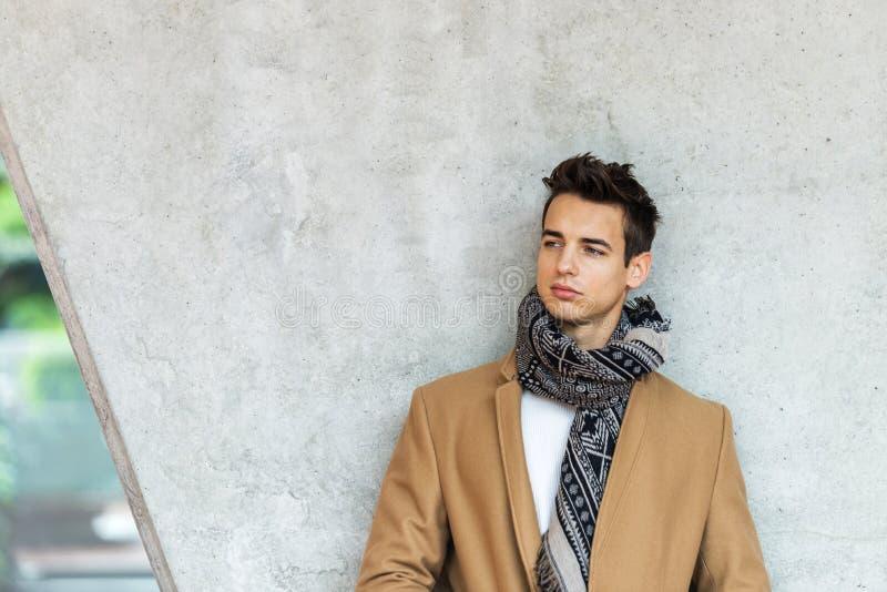 Vista frontale del cappotto d'uso d'avanguardia e della sciarpa del giovane che si appoggiano una parete mentre distogliendo lo s fotografie stock