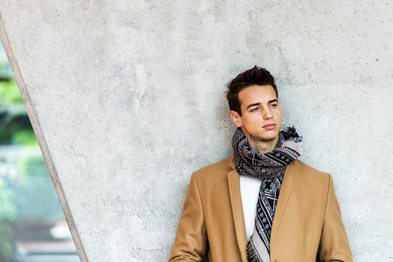 Vista frontale del cappotto d'uso d'avanguardia e della sciarpa del giovane che si appoggiano una parete mentre distogliendo lo s immagini stock