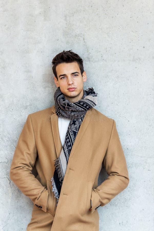 Vista frontale del cappotto d'uso d'avanguardia e della sciarpa del giovane che si appoggiano una parete mentre guardando macchin fotografia stock