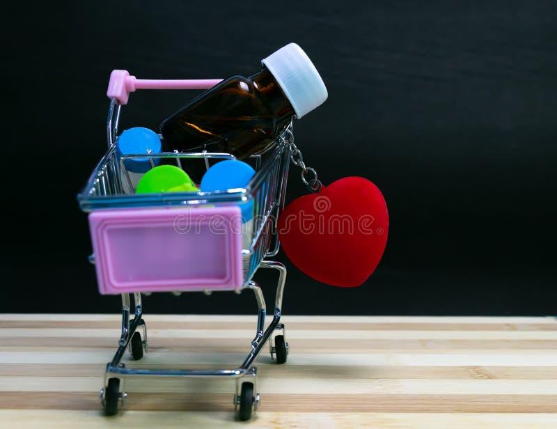 Vista frontale del carretto di Mini Shopping riempita di bottiglie della medicina omeopatica delle pillole con cuore rosso su leg fotografia stock libera da diritti