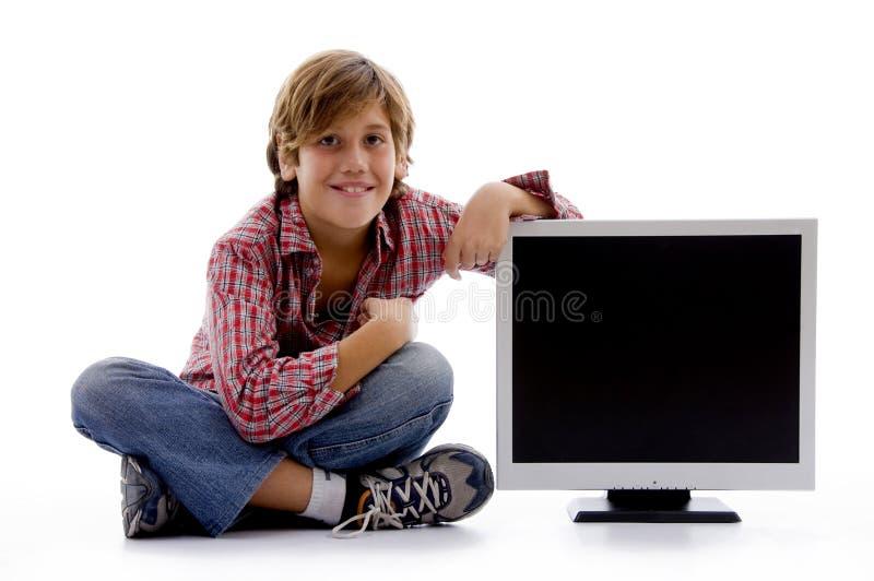 Vista frontale del ragazzo di seduta con lo schermo dell'affissione a cristalli liquidi fotografie stock libere da diritti