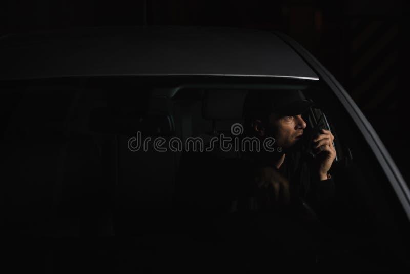 vista frontale dell'agente investigativo privato maschio in cappuccio facendo uso del walkie del talkie fotografie stock libere da diritti