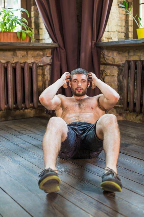 Vista frontale dell'uomo che fa gli esercizi addominali sul pavimento a casa fotografie stock libere da diritti