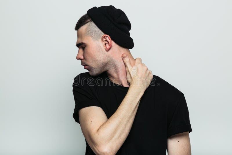 Vista frontale dell'uomo girato che tocca il suo collo fotografia stock