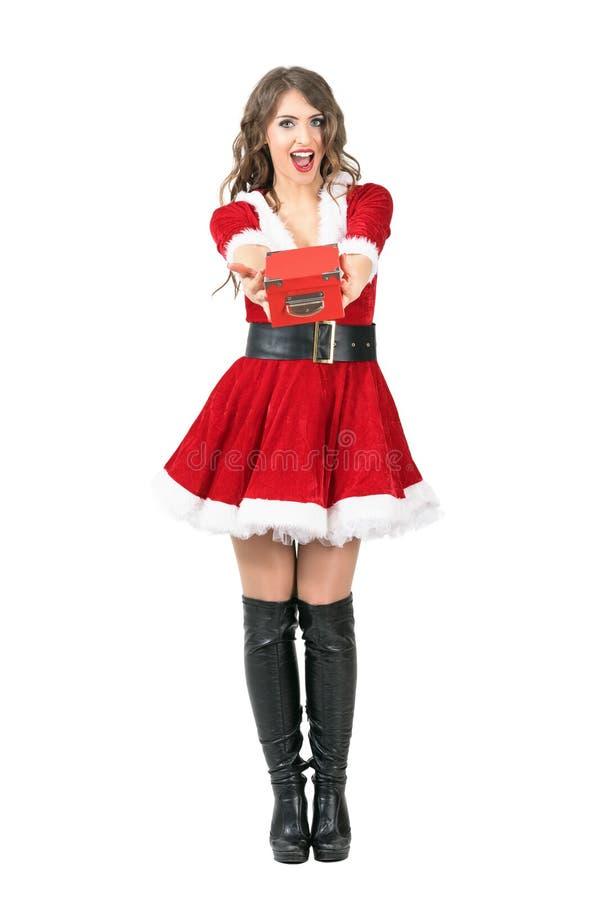 Vista frontale della donna stupita di Santa Claus che dà il regalo di Natale che esamina macchina fotografica immagini stock libere da diritti