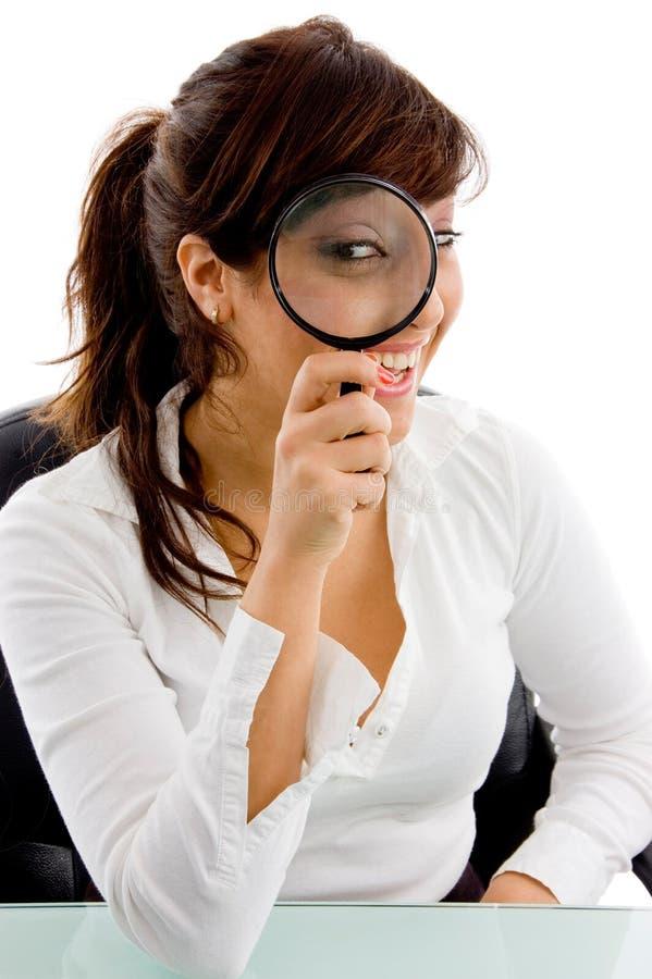 Vista frontale della femmina che osserva tramite l'obiettivo fotografie stock