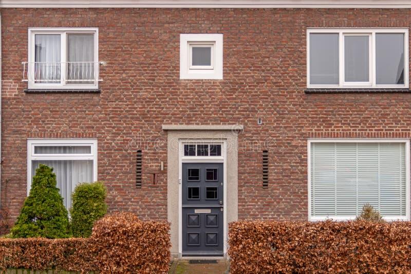 Vista frontale delle case con mattoni a vista olandesi comuni con alcuni cespugli piacevoli del frontyard fotografie stock