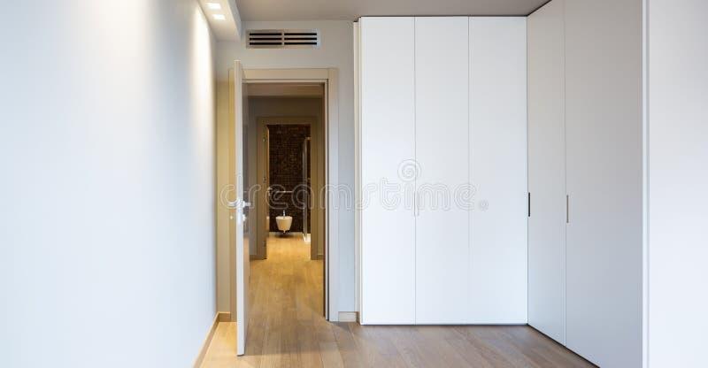 Vista frontale di stanza moderna con il grande guardaroba fotografia stock