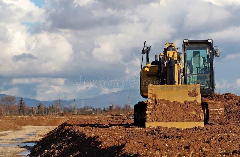 Vista frontale di un escavatore, con la cabina vuota accesa, fra un cielo nuvoloso ed il suolo della sporcizia immagine stock libera da diritti