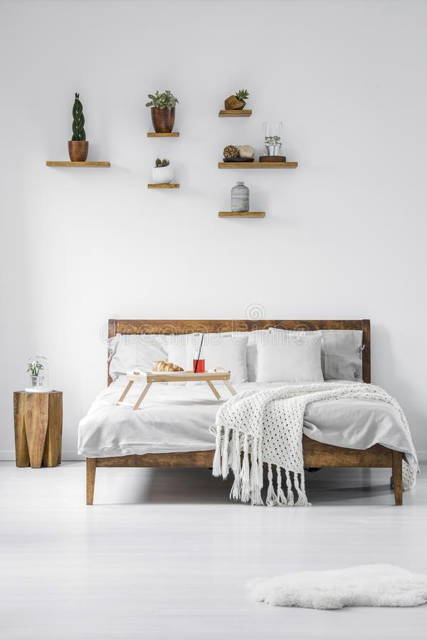 Vista frontale di un letto matrimoniale incorniciato di legno con tela, cuscini e immagine stock