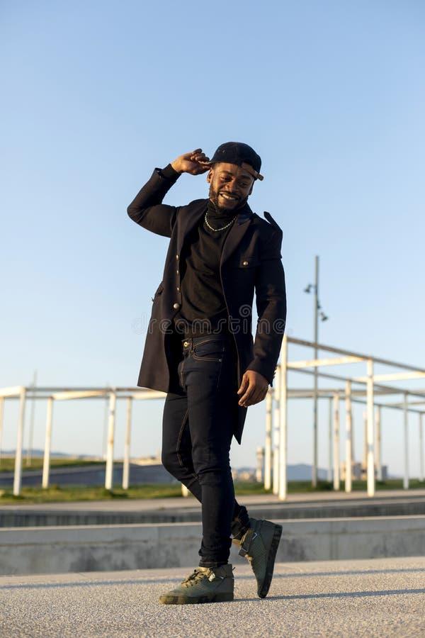 Vista frontale di un uomo barbuto nero che tiene un cappello mentre ballando e godendo contro il cielo blu in un giorno soleggiat fotografia stock